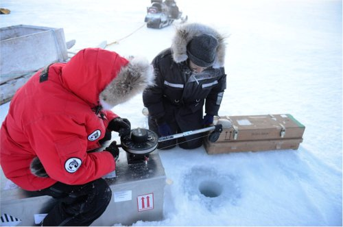 Eric Solomon, Vancouver Aquarium, and Bill Williams, DFO, lower the CTD through a hole in the ice.