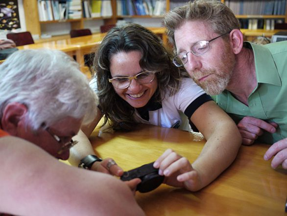 From L-R: researchers Jennifer Mather, Tatiana Leite and David Scheel, looking at photos of an octopus from local waters.