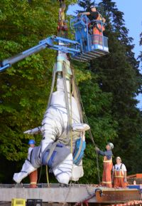 The statue was wrapped in protective covering and moved with a crane.