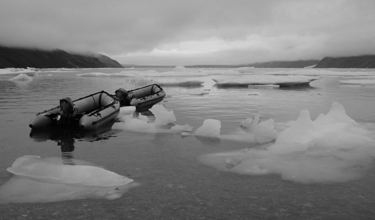 Zodiacs sit unused in a fiord full of ice.
