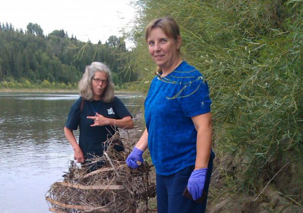 Team members Raquel and Kathy help haul a mattress bedspring from the North Saskatchewan River.